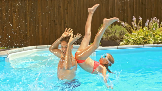 SLO MO Father throwing his daughter off his shoulders into the pool video