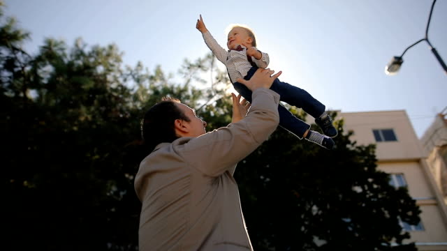 Father throwing son into air after work.Happiness,together video