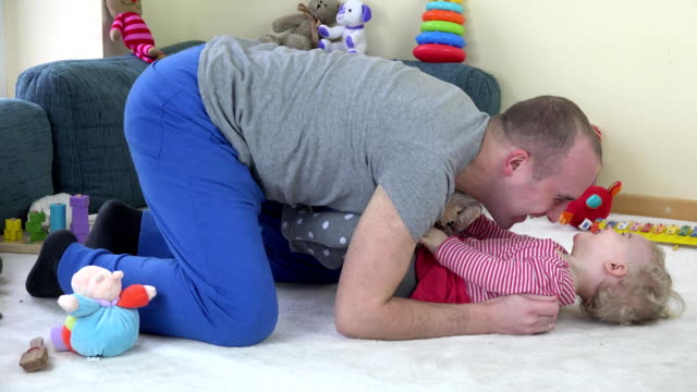 father tickle toddler daughter on carpet between toys at home. video