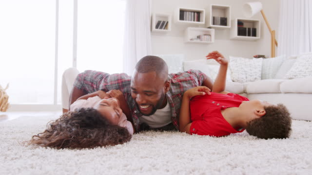 Father Tickling Children As They Play Game In Lounge Together Father tickling son and daughter lying on lounge rug at home - shot in slow motion lying down stock videos & royalty-free footage