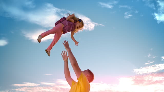 SLO MO Father tossing his daughter into the air in sunshine video
