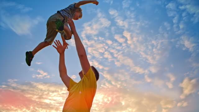 SLO MO pai mostrando seu filho no ar ao pôr do sol - vídeo