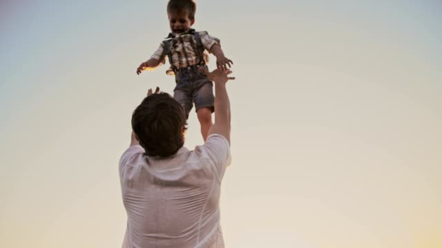 SLO MO Father tossing his son up in the air video