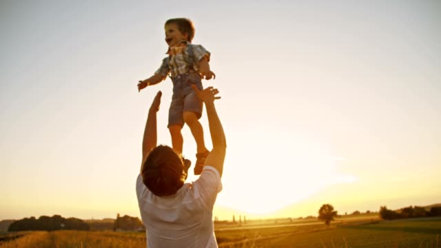 slo mo padre lancio suo figlio up in the air - fiducia video stock e b–roll