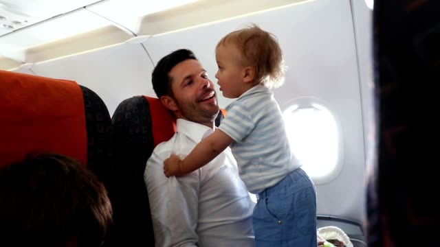 Father traveling with children and baby by airplane. Dad holding and playing with baby while waiting for plane's departure video