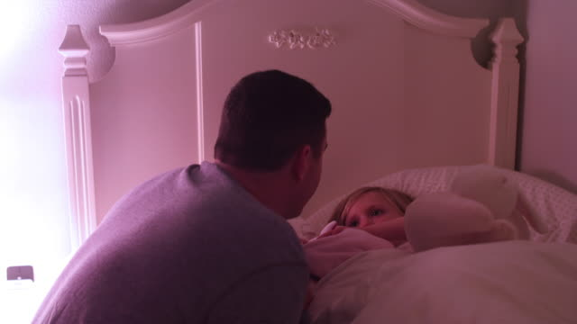 A father tucks his daughter into bed and gives her a goodnight kiss video