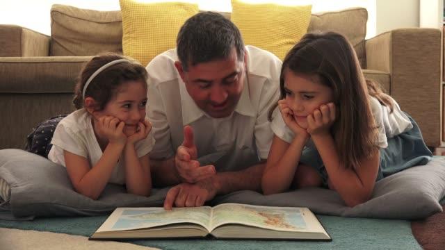 vídeos de stock, filmes e b-roll de pai ensinando filhas em casa - dia dos pais