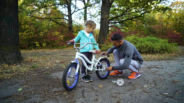 Father unscrewing supporting wheels on bicycle of little daughter video
