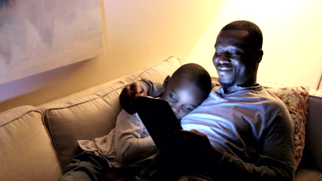 Father using digital tablet, son sleeping An African-American father using an e-reader or digital tablet, lying on his back on a sofa with his son who has fallen asleep. He kisses his son gentle on the top of his head. The child is 7 years old and dad is a mid adult man in his 30s. black people stock videos & royalty-free footage