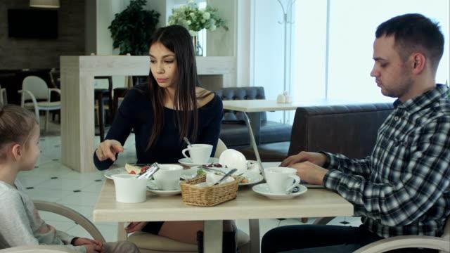 stockvideo's en b-roll-footage met vader met zijn laptop zittend met zijn vrouw en dochter in café. vrouw begrijpen en niet storend hem - kids online abuse