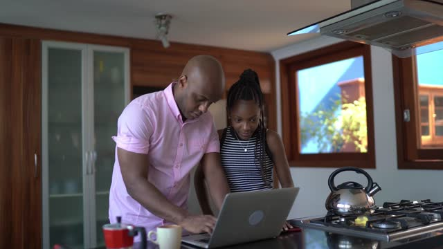 Father using laptop in the kitchen and talking to teenager daughter at home
