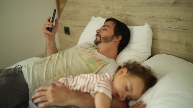 Father using smart phone while his son sleeping next to him in bed