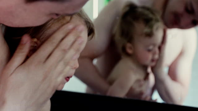 Father washing face of boy with standing mirror video