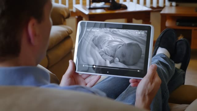 Father Watches Sleeping Baby on Monitor on Tablet PC video
