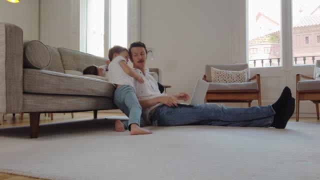 Vater trägt einen Helm, der versucht, von zu Hause aus zu arbeiten – Video