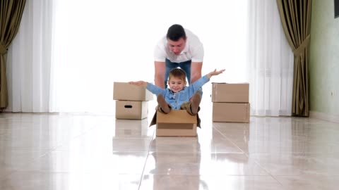 father wearing white shirt rides smiling son in craft box father wearing white shirt rides smiling and crying son in big cardboard box on floor of new house lounge slow motion art and craft stock videos & royalty-free footage