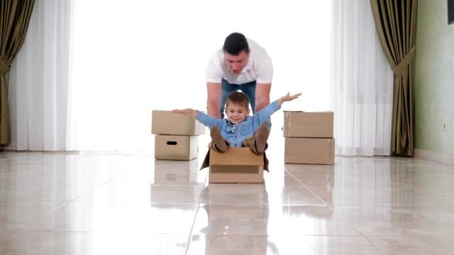 padre che indossa camicia bianca cavalca figlio sorridente in scatola artigianale - arti e mestieri video stock e b–roll