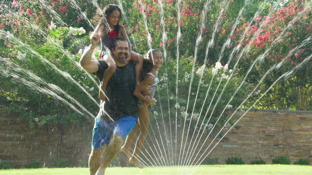 vídeos de stock e filmes b-roll de father with 2 daughters playing in a water sprinkler - jardim particular