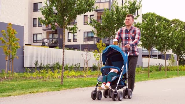 şehirde bebek arabası ve kahve bebek ile baba - estonya stok videoları ve detay görüntü çekimi