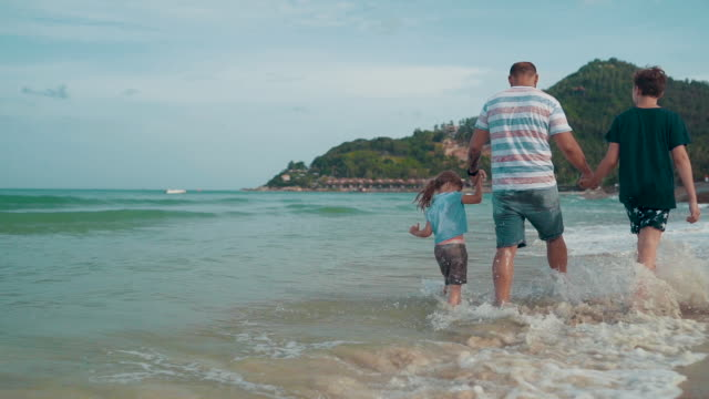 father with children enjoy walking on the beach - padre single video stock e b–roll