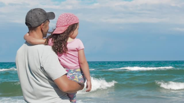 Father with daughter looking at sea.