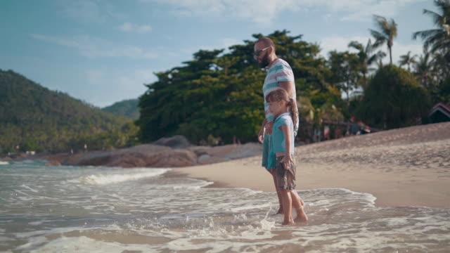 vídeos de stock, filmes e b-roll de pai com filha brincando na praia - férias na praia