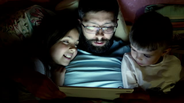 father with little children surfing on tablet computer before sleeping - oglądać filmów i materiałów b-roll