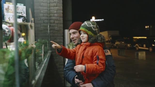 vater mit kleinen sohn betrachten schaufenster auf weihnachten - schaufenster stock-videos und b-roll-filmmaterial