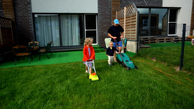 Father with son cut grass and super-girl daughter with cloak and toy lawn mower