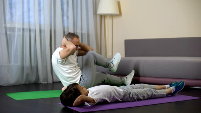 Father with son doing abdominal crunches at home, showing benefit of sports video