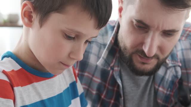 far med sonen gör läxor i bok - människokroppsdel bildbanksvideor och videomaterial från bakom kulisserna