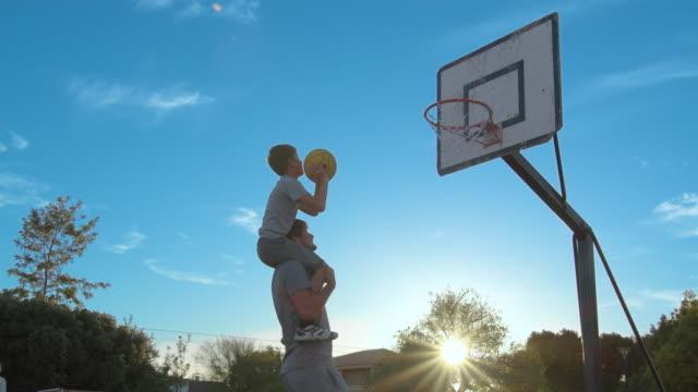 far med sonen njuta av en dag i parken och spela basket - naturparksområde bildbanksvideor och videomaterial från bakom kulisserna