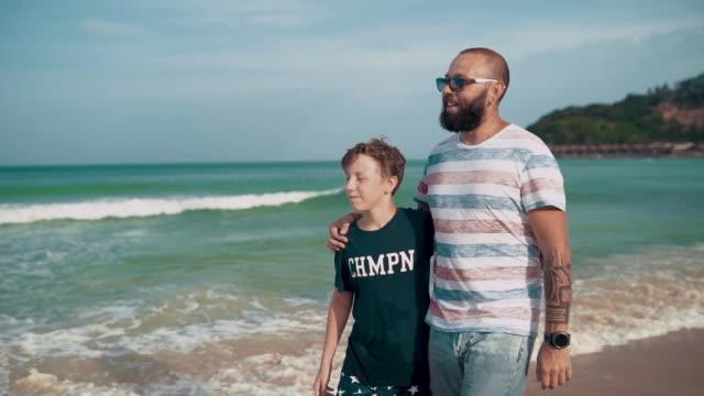 far med son njuta av promenader på stranden - parent talking to child bildbanksvideor och videomaterial från bakom kulisserna
