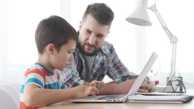 father with son learning to use laptop - online learning stock videos & royalty-free footage