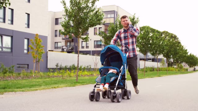 father with stroller calling on smartphone in city