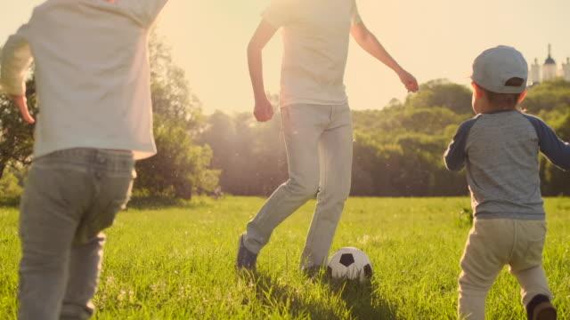 stockvideo's en b-roll-footage met vader met twee zonen voetballen in de wei - wit t shirt