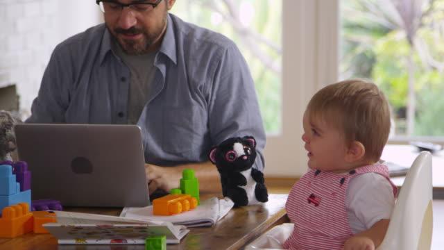 far som jobbar hemifrån på laptop som son leker med leksaker - working from home bildbanksvideor och videomaterial från bakom kulisserna