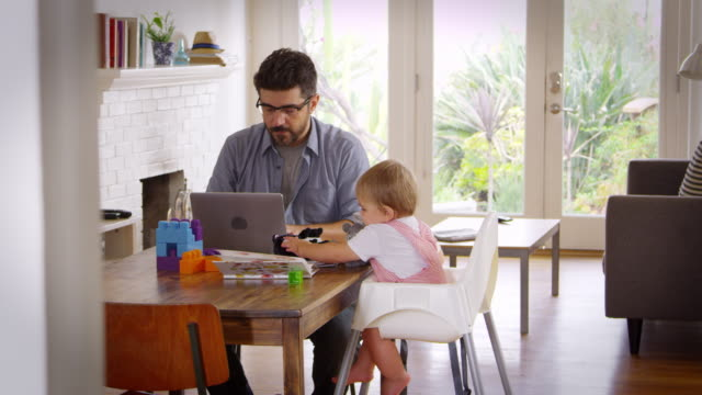 Father Working From Home On Laptop As Son Plays With Toys