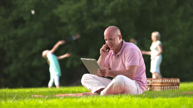 HD DOLLY: Father Working While Having Picnic With Family video