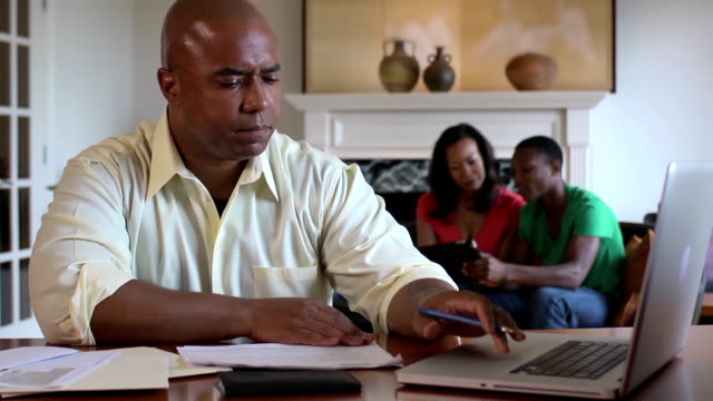 Father Works on Home Finances with Family in Background video