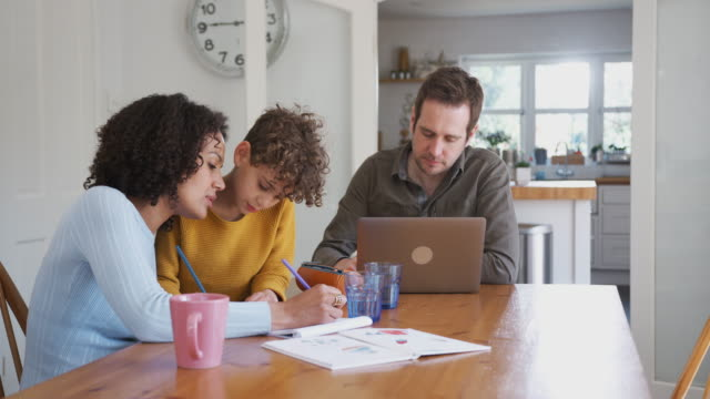 father works on laptop as mother helps son with homework on kitchen table - family home video stock e b–roll