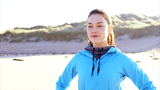 stockvideo's en b-roll-footage met vermoeid fit vrouw genieten van frisse lucht na het uitvoeren van op strand - handen op de heupen