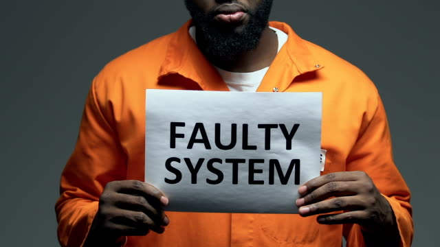 Faulty system phrase on cardboard in hands of Afro-American prisoner, disorder Faulty system phrase on cardboard in hands of Afro-American prisoner, disorder civil rights stock videos & royalty-free footage