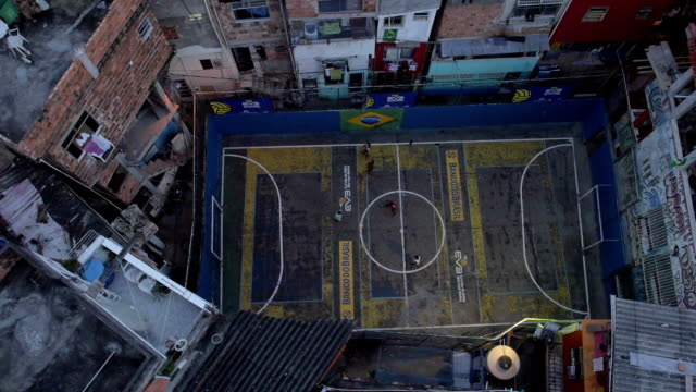 Favela Football: Panning aerial drone shot of football pitch in a Rio de Janeiro favela