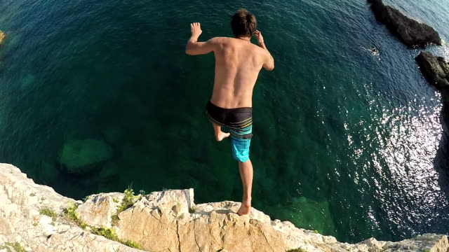 slow motion close up: fearless man jumping from high rocky ledge into the ocean - cliffs stock videos & royalty-free footage