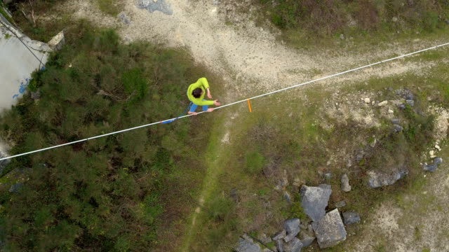 AERIAL: Fearless slackliner sitting on highline over abyss and standing up video