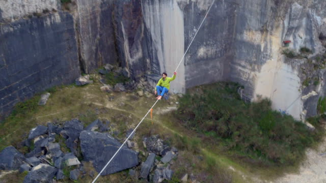 AERIAL: Fearless slackliner sitting on highline over abyss, waving, standing up video