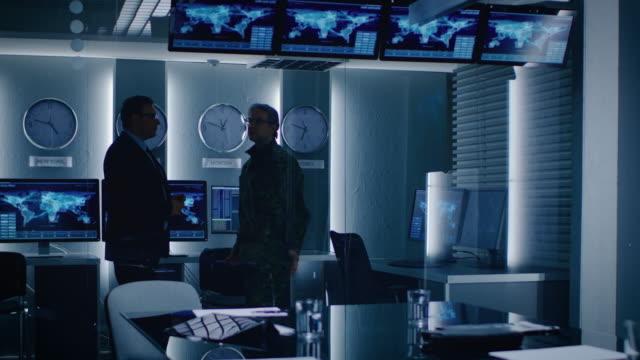 モニター ルームで軍人に連邦政府の特別なエージェント協議。背景忙しいシステム コントロール センターのモニターのデータ フローを示します。 - 軍事点の映像素材/bロール