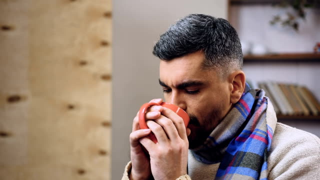 Feeble diseased male drinking hot tea with medicine to remove influenza symptoms video