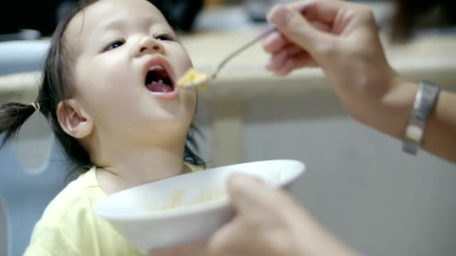 Feeding baby girl(12-23 months) eating some solid food